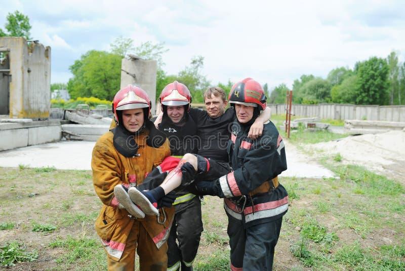 救助者和志愿者和军事转移受伤的人到安全的地方 示范性的锻炼 免版税库存图片