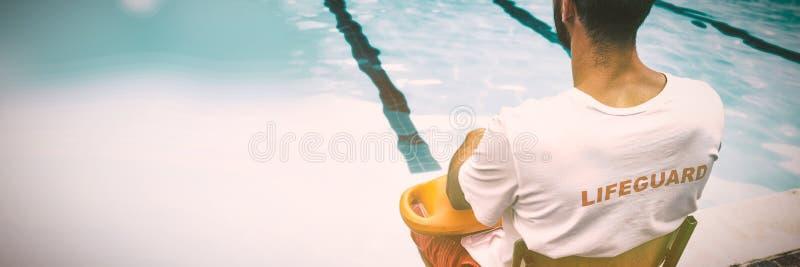 救生员坐与抢救浮体的椅子在游泳池边 免版税库存图片