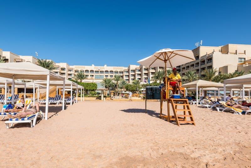 救生员坐在海滩的监视塔在红海的洲际的亚喀巴旅馆在亚喀巴,约旦 免版税库存图片