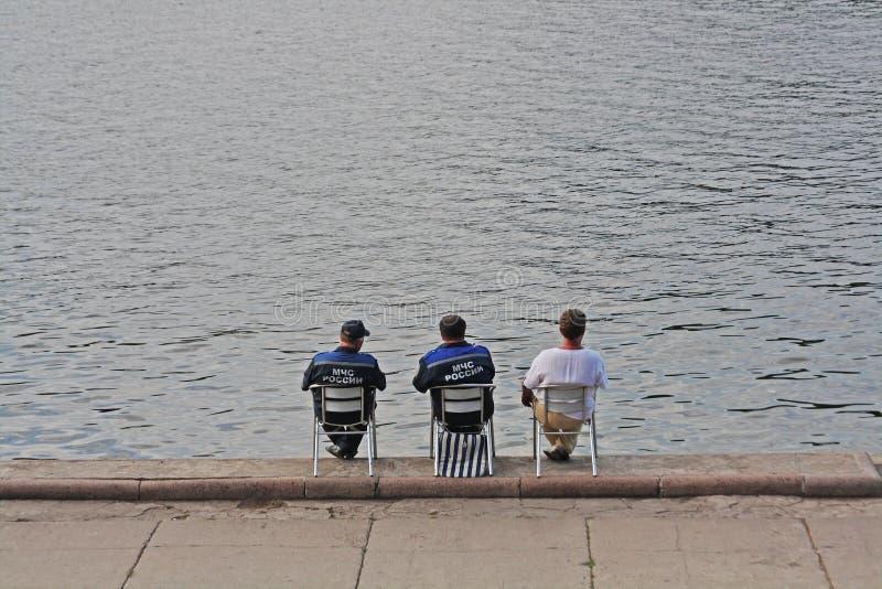 救生员背面图在椅子在水附近坐莫斯科河的河岸在莫斯科 免版税图库摄影