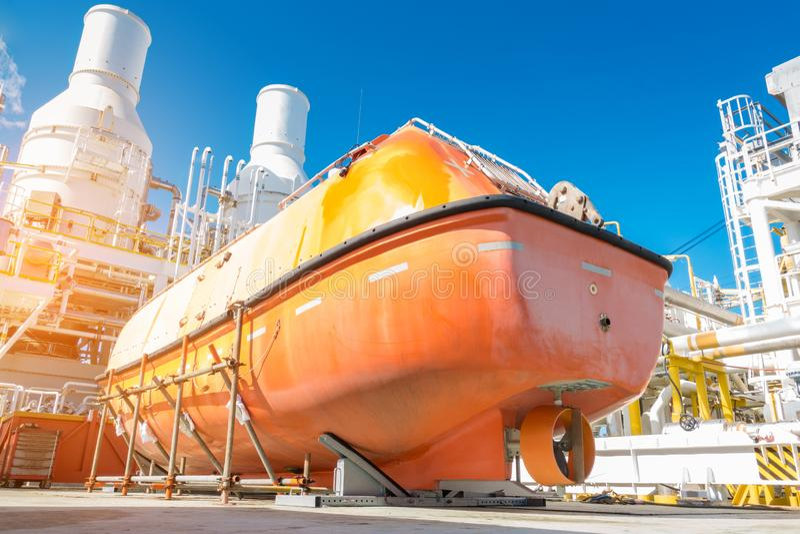 救生船或救助艇在脚手架支持在近海油和煤气中央处理平台一会儿检查 免版税库存照片