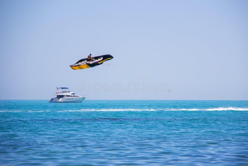 救生衣的年轻人在backgrou获得乐趣并且乘坐一种大黑和黄色飞行香蕉船水吸引力在海 库存照片