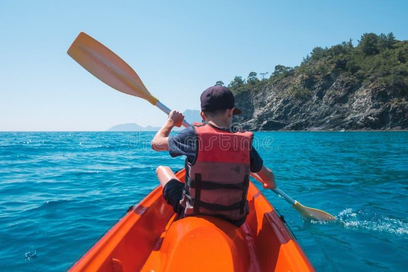 救生衣的男孩在橙色皮船 免版税库存图片