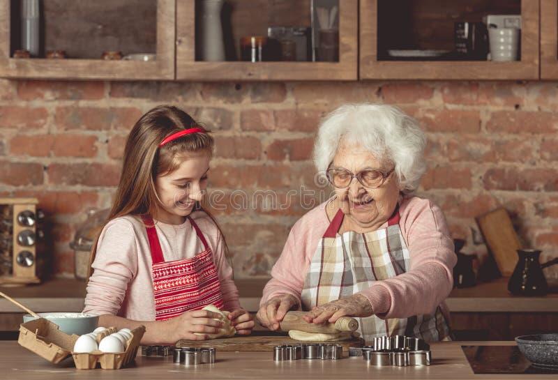教一个小女孩的年长妇女烘烤曲奇饼 库存图片