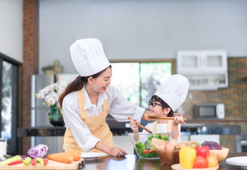 教一点儿子的幸福家庭亚裔妈妈烹调沙拉菜准备健康食品 图库摄影