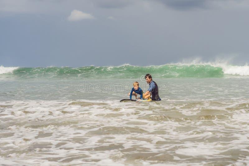 教他五岁的儿子如何的父亲或辅导员在海冲浪在度假或假日 旅行和体育与 库存图片