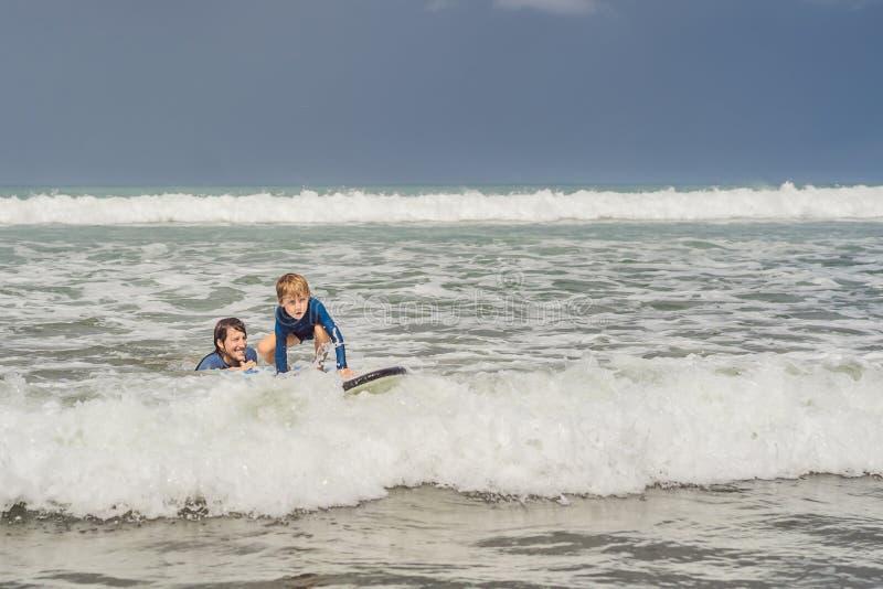 教他五岁的儿子如何的父亲或辅导员在海冲浪在度假或假日 旅行和体育与 库存照片