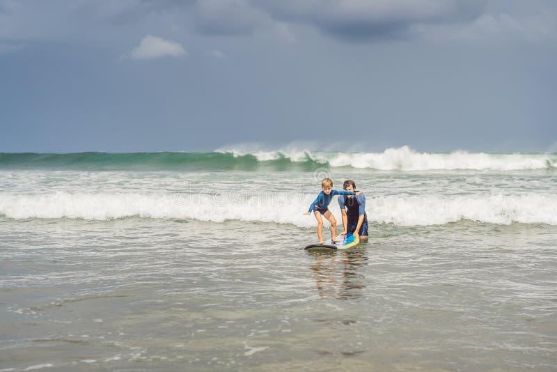 教他五岁的儿子如何的父亲或辅导员在海冲浪在度假或假日 旅行和体育与 免版税库存照片