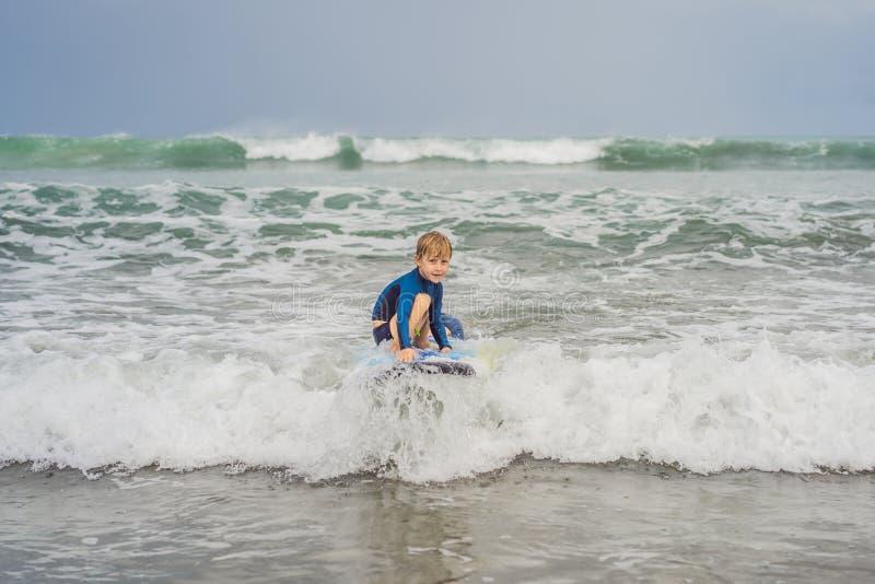 教他五岁的儿子如何的父亲或辅导员在海冲浪在度假或假日 旅行和体育与 免版税图库摄影