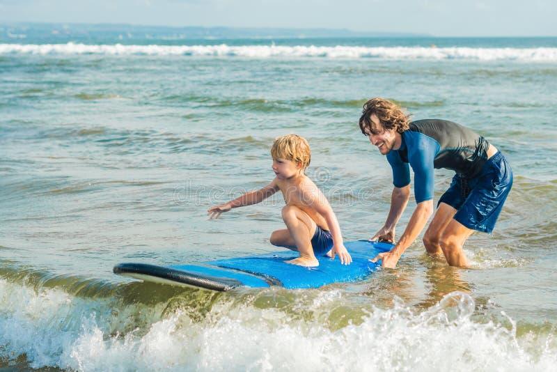教他四岁的儿子如何的父亲或辅导员在海冲浪在度假或假日 旅行和体育与 图库摄影