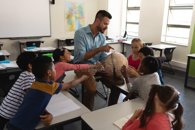 教他的关于地理的男老师孩子通过使用地球在教室 免版税图库摄影