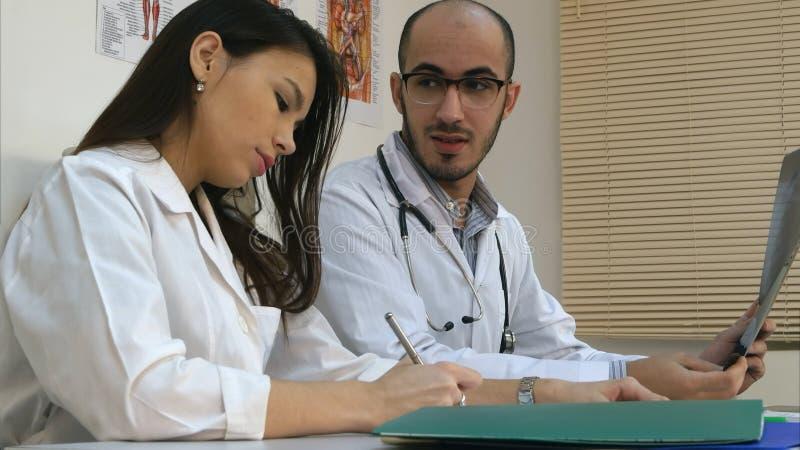 教他的女性实习生如何的男性医生分析X-射线图象 免版税库存图片