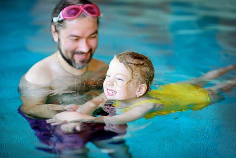 教他的小女儿的愉快的父亲游泳 学会活跃愉快的孩子游泳 免版税库存图片