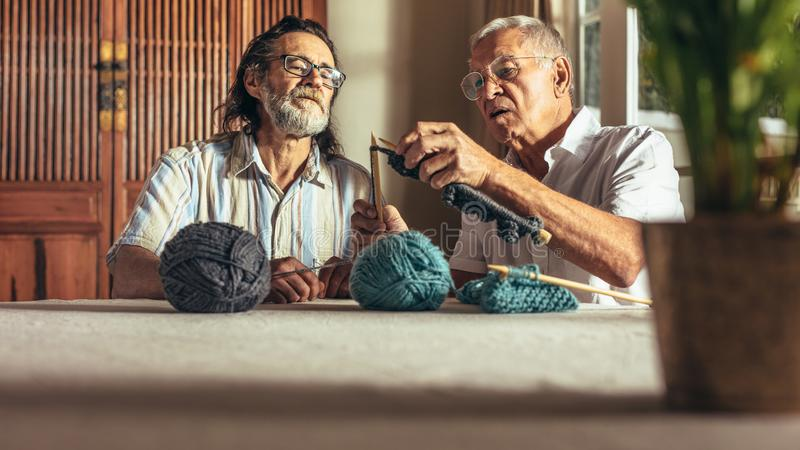 教他的朋友艺术编织的老人 库存照片