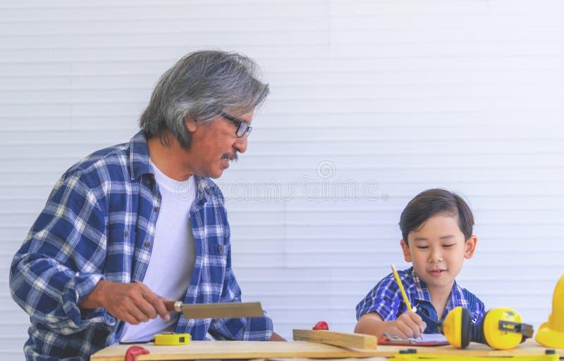 教他的男孩的建造者祖父在建筑木制品工具工作 免版税图库摄影