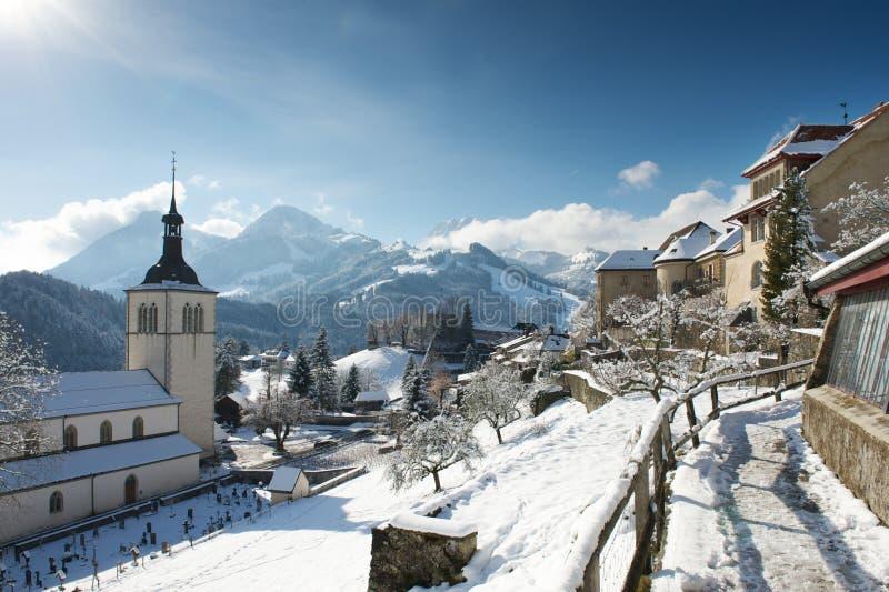教会和城堡的看法在格律耶尔村庄, Switze 免版税库存照片