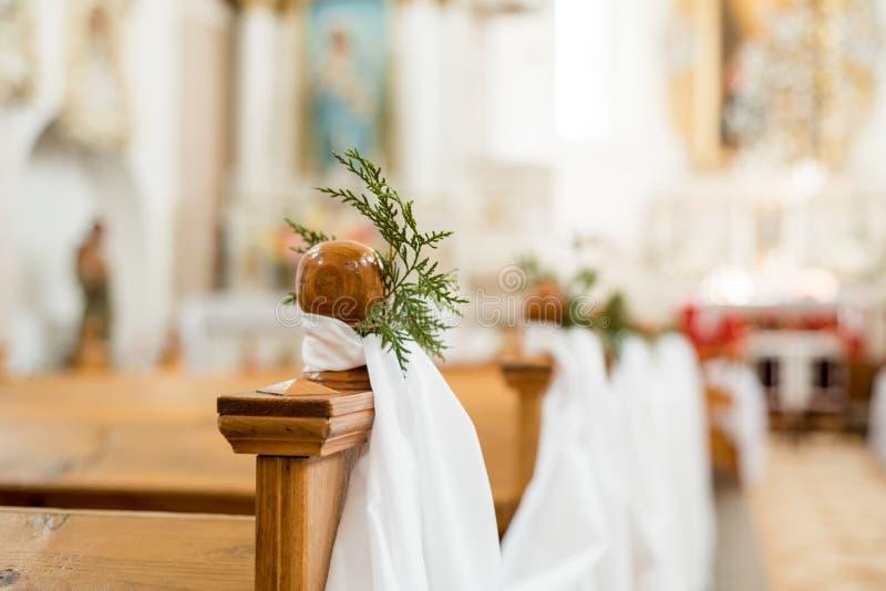 教会婚礼 明亮的寺庙 浅深度的域 在长凳和椅子的白色装饰品 婚礼绿色和花 图库摄影