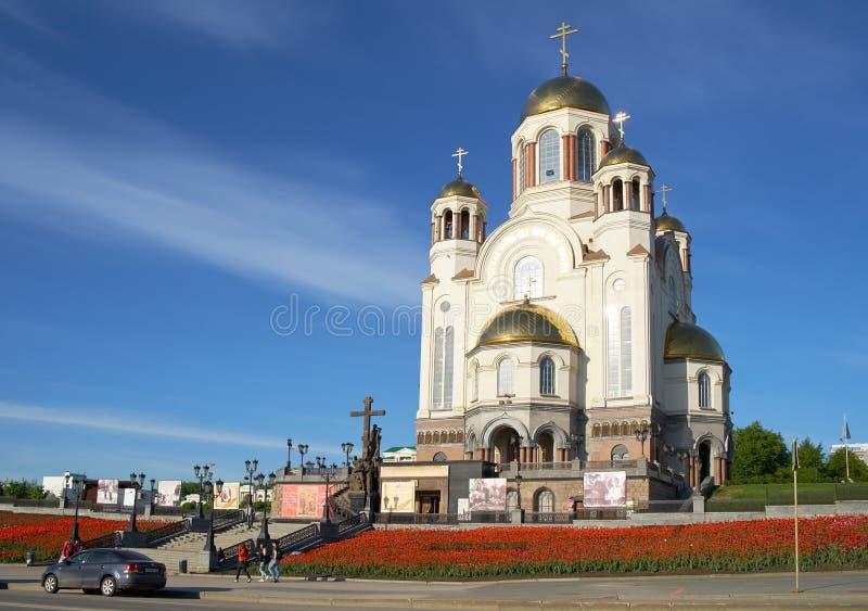 教会的看法血液的在有开花的郁金香的春天在前景 Ekaterinburg,俄国 免版税库存照片
