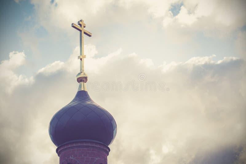 教会的黑圆顶有一个金黄十字架的在与白色云彩的天空背景 老红砖的塔根据t的 免版税库存图片
