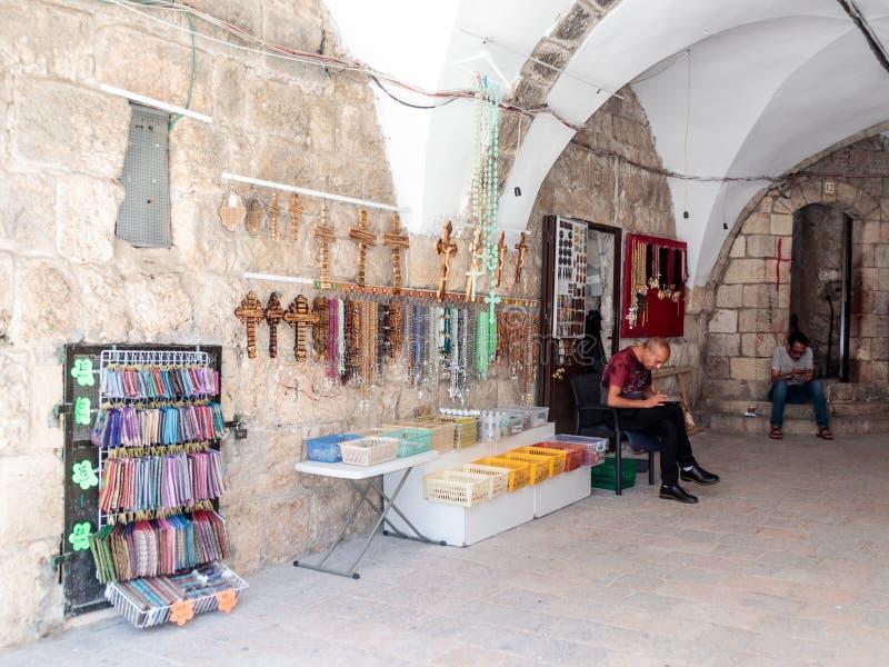 教会纪念品商店的卖主在他的手机坐并且看在老城耶路撒冷,以色列 图库摄影