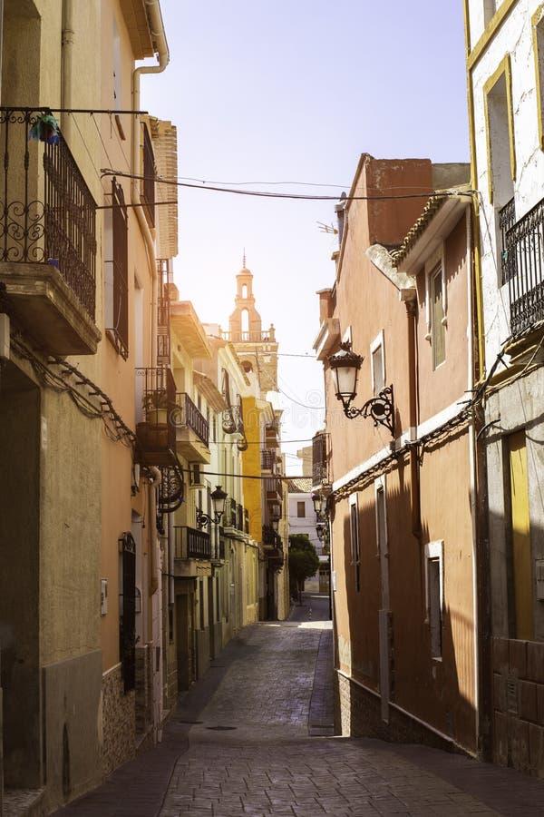 教会能被看见在Releu老镇的舒适街道末端太阳的光芒的 地中海建筑学 免版税库存照片