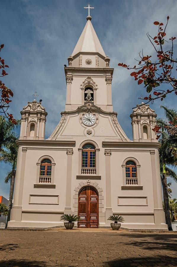 教会门面和钟楼在一个小鹅卵石前面摆正与常青庭院,在一个晴天在São曼纽尔 图库摄影