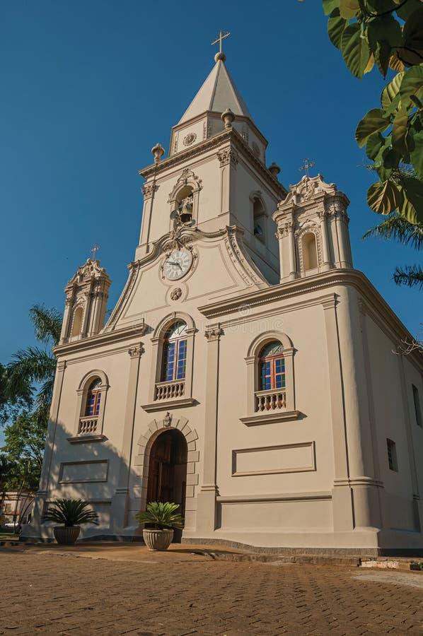 教会门面和钟楼在一个小鹅卵石前面摆正与常青庭院,在一个晴天在São曼纽尔 库存照片