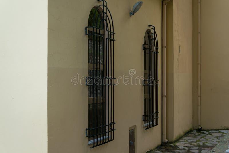 教会门面-与防止通入的金属栏杆的大窗口接近的看法  免版税图库摄影
