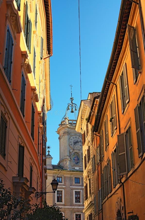 以教会结束的狭窄的街道 塔加冠与异常的形状圆顶  罗马 意大利 库存照片