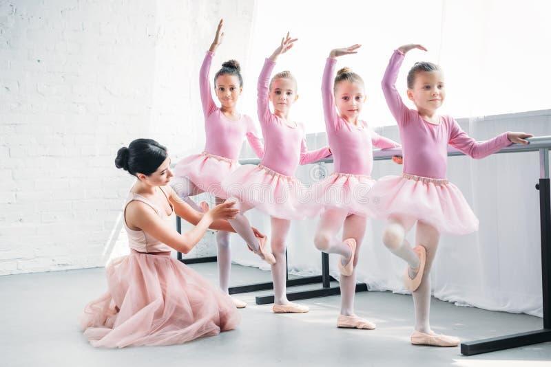 教可爱的孩子在芭蕾的年轻女人跳舞 免版税图库摄影