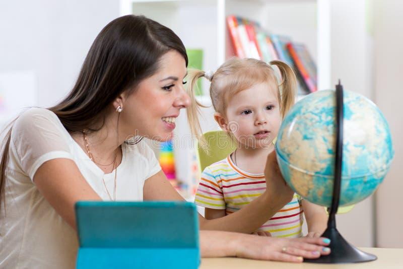教和显示地球的俏丽的妇女对孩子 免版税库存照片