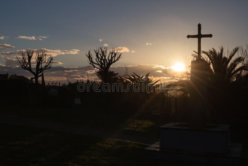 教堂和十字架美丽的剪影在日出在大西洋海岸在bidart,巴斯克国家 图库摄影