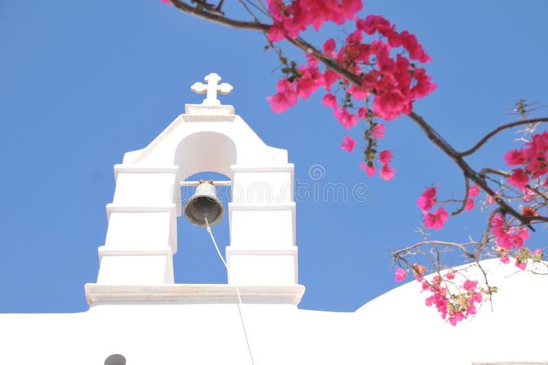 教堂钟和桃红色花在米科诺斯岛,希腊 免版税库存照片