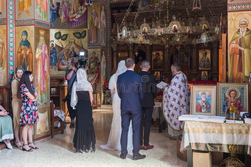教士读一个祷告在正统传统举行的婚礼在十二位传道者的东正教修道院里 免版税库存照片