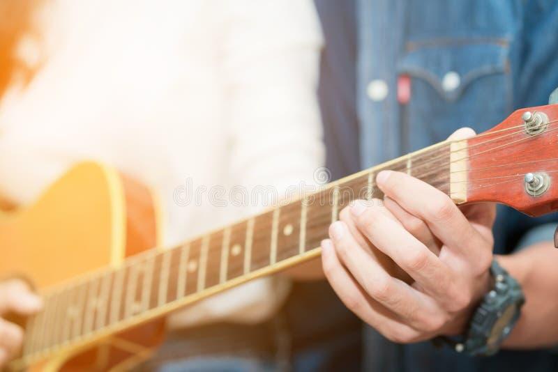 教声学吉他的夫妇的手 库存照片