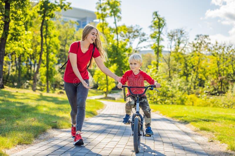 教她的儿子如何的年轻母亲骑一辆自行车在公园 免版税库存图片