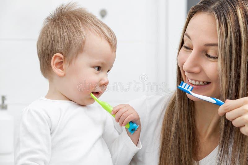 教她的儿子如何的愉快的母亲丛生牙 库存照片