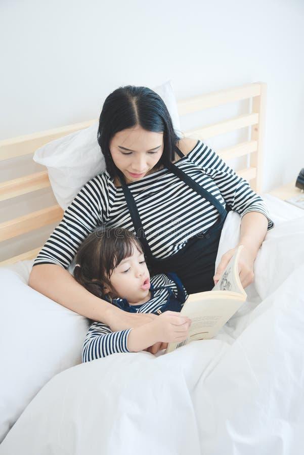 教她的女儿的亚裔母亲对读一本床时间故事书在假日 免版税库存图片