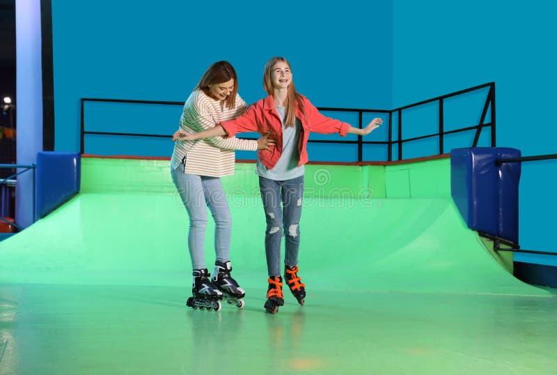 教她的女儿的妇女在路辗溜冰场 库存图片