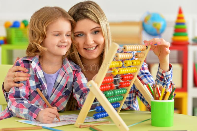 教她的女儿的母亲画象使用算盘户内 免版税库存图片