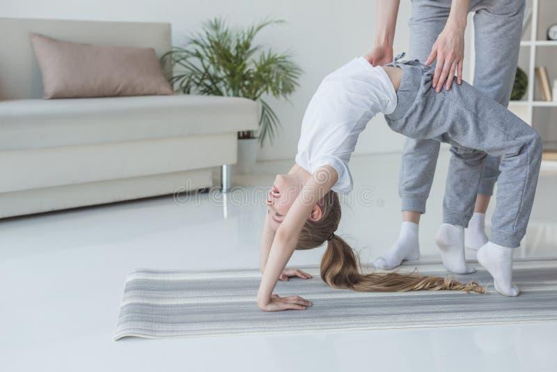 教她的女儿的母亲站立在瑜伽轮子姿势 库存图片