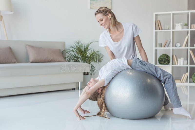 教她的女儿的母亲站立在瑜伽轮子姿势 图库摄影