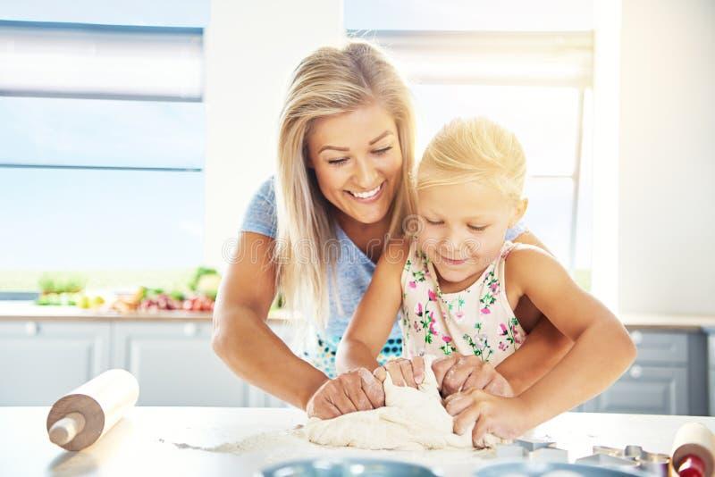 教她的女儿的崇拜的年轻母亲烘烤 免版税库存图片