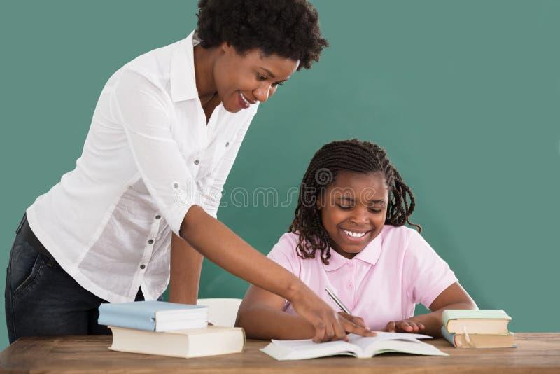 教她的学生的愉快的老师 免版税库存图片