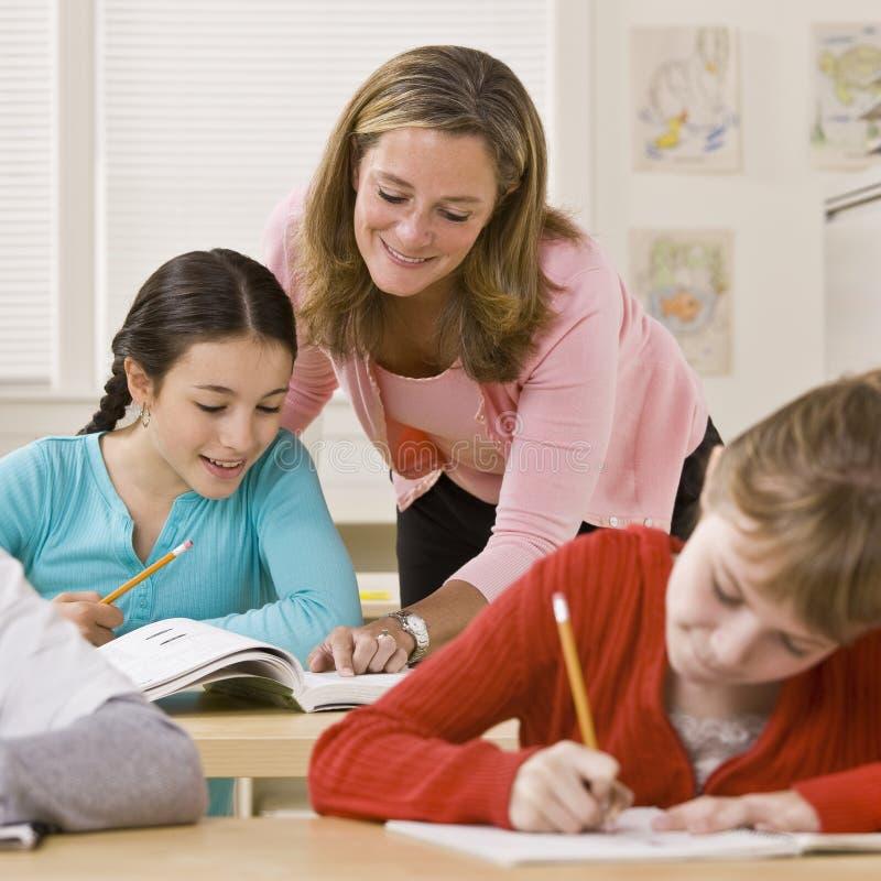 教室帮助的实习教师 免版税图库摄影