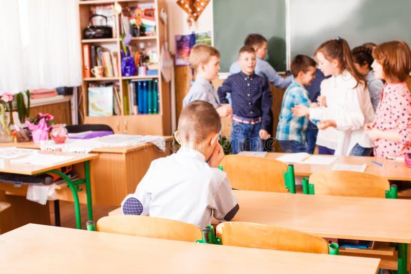 教室的孤独的哀伤的男孩 免版税库存图片