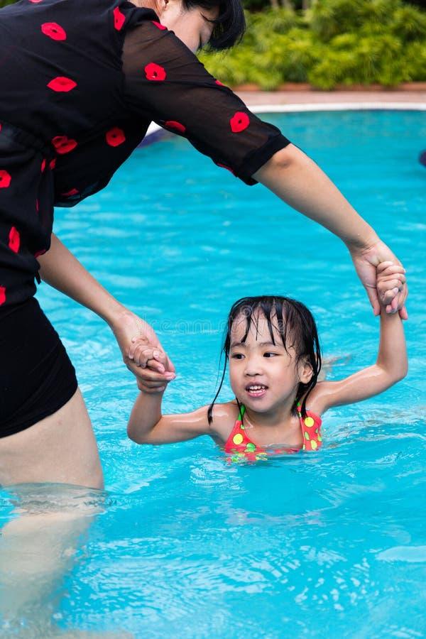 教小女孩游泳的亚裔中国妈妈在水池. 愉快, 少许.
