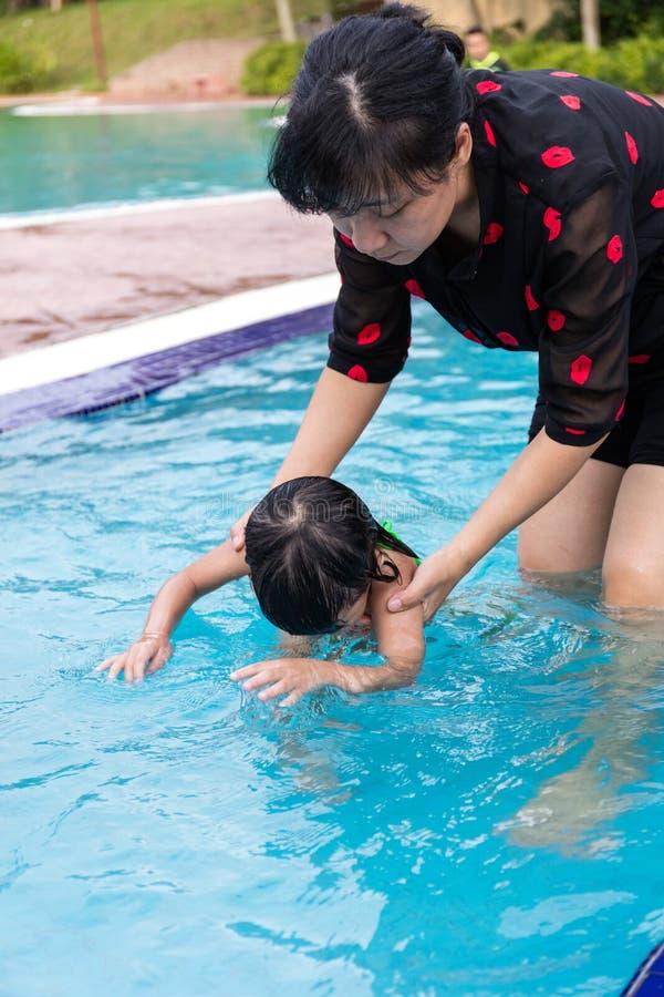 教小女孩游泳的亚裔中国妈妈在水池