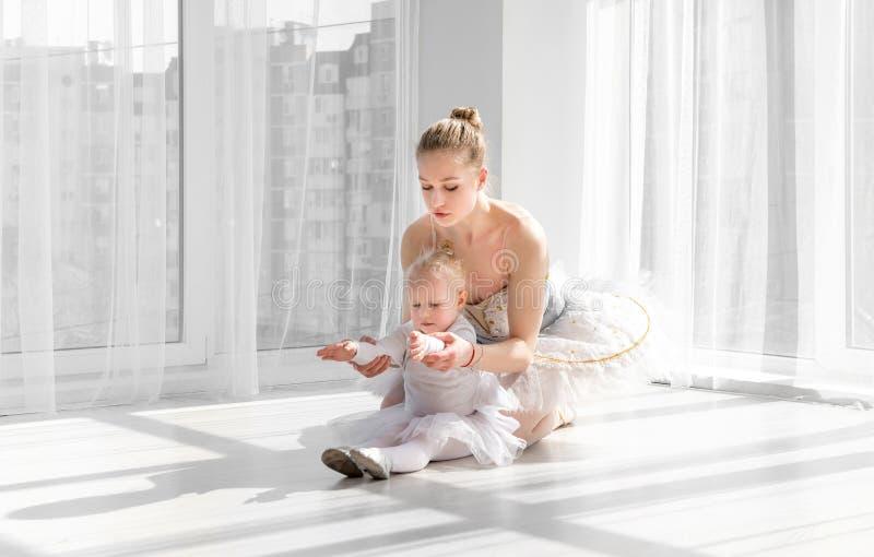 教小女孩的女性跳芭蕾舞者做舒展的exarcises 免版税库存照片