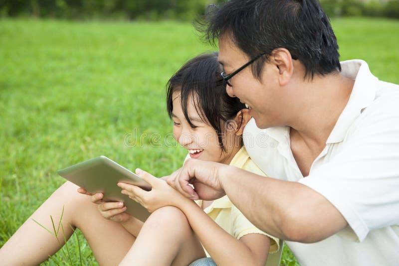 教小女孩的父亲使用片剂个人计算机 免版税库存照片